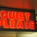 red neon sign saying quiet please to illustrate blog how loud is too loud