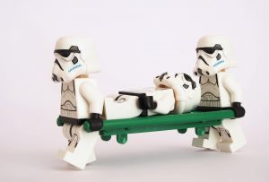 Two Lego Stormtroopers carrying another lego stormtrooper on a stretcher to illustrate first aid at work blog
